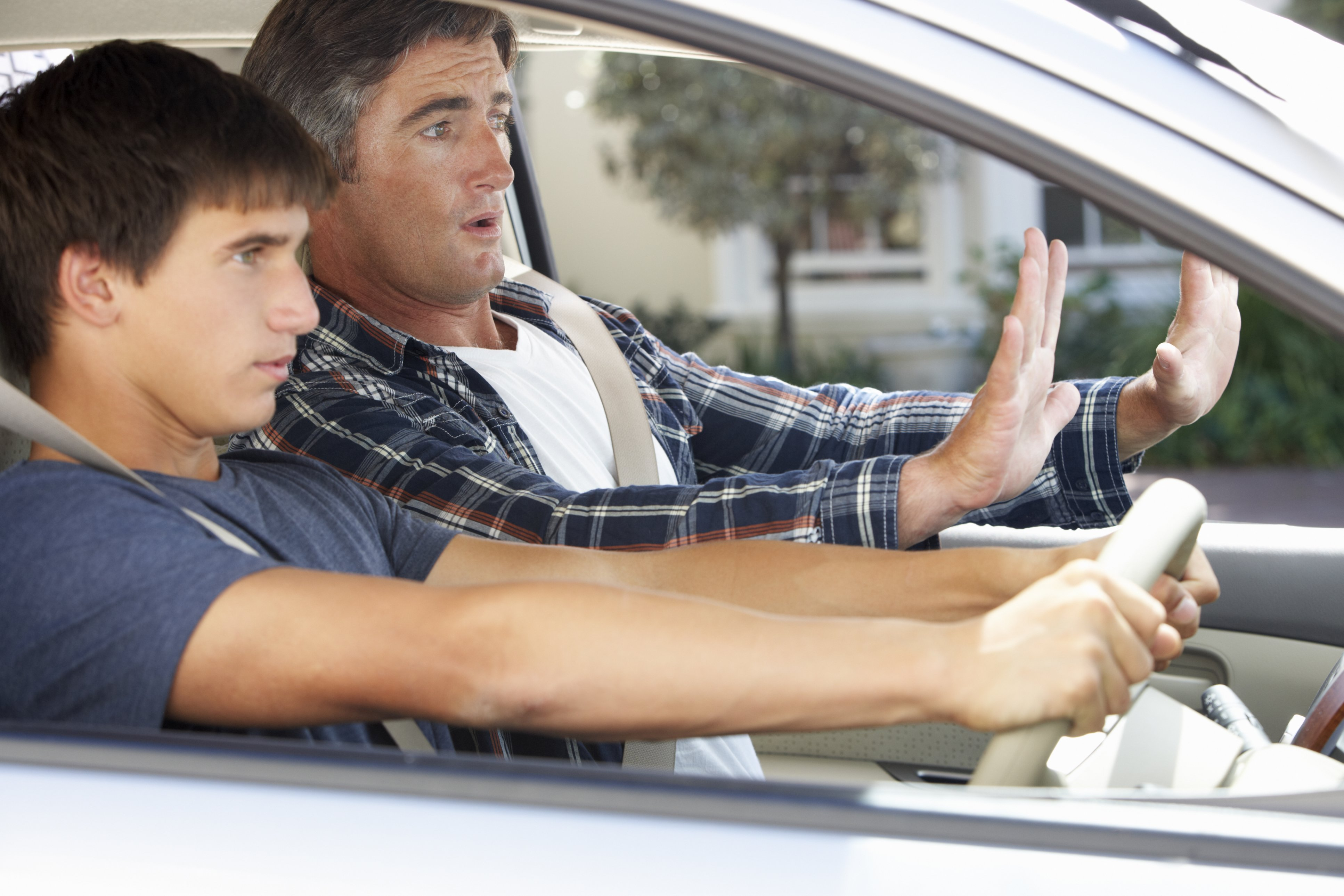 Nervous Father Teaching Teenage Son To Drive