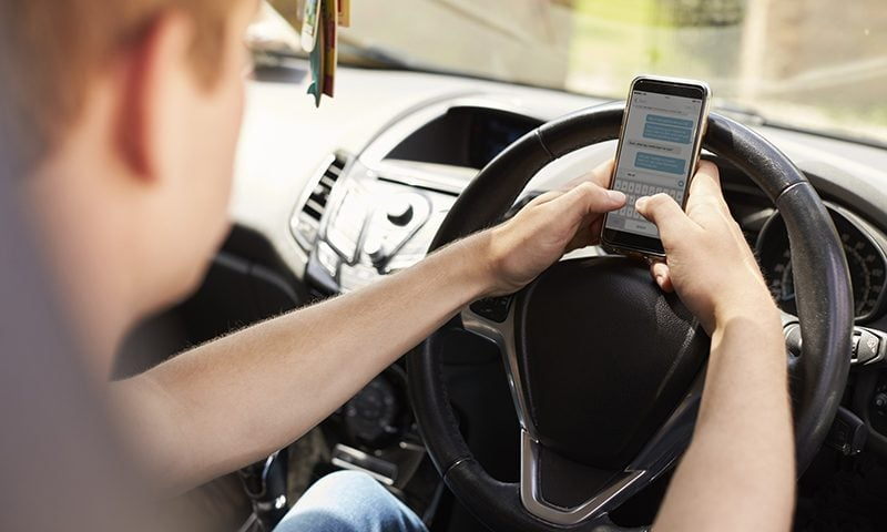 Young man sending text message on mobile phone while driving his car