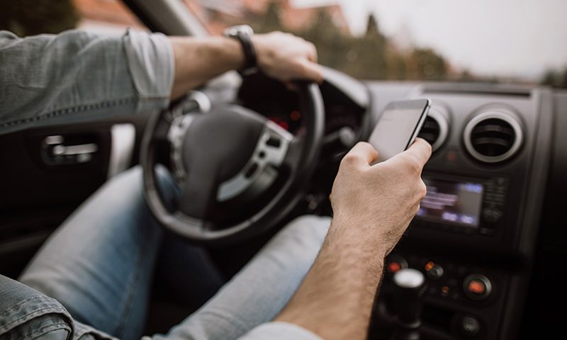 A driver uses a mobile phone at the wheel.