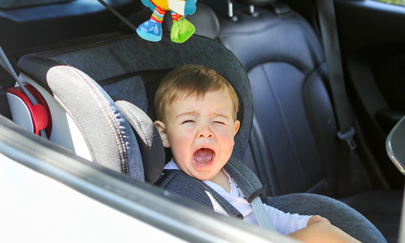 Image Caption Parents struggle to get their kids into the car.