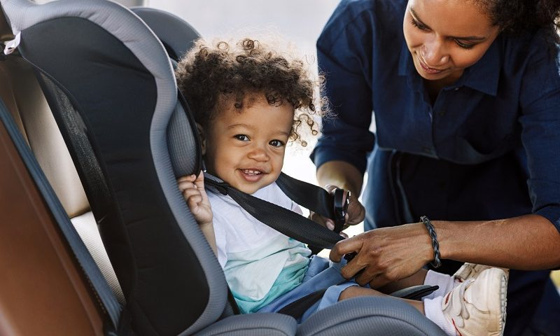 Parent strapping child into car seat.
