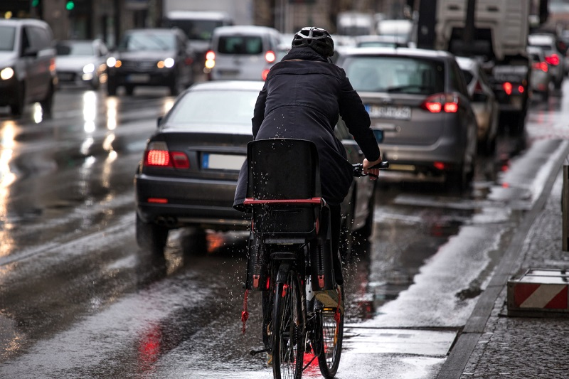 Cyclist on rainy street.
