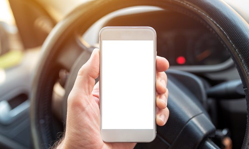 Driver holding smartphone.