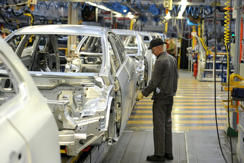 Man inspects car on production line in factory