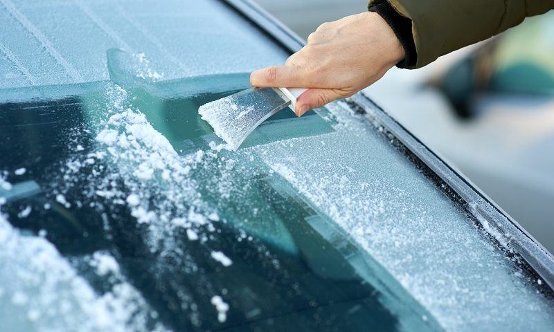Scraping ice off the windshield.