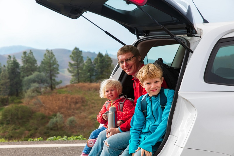 Father with kids on driving trip
