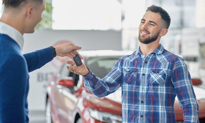 Car salesman handing over car key to customer