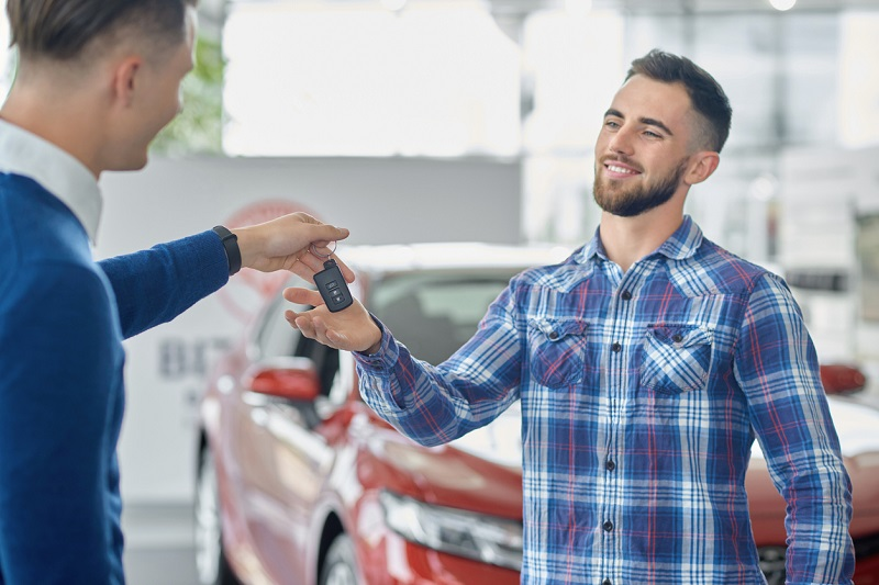 Car salesman handing over car key to customer