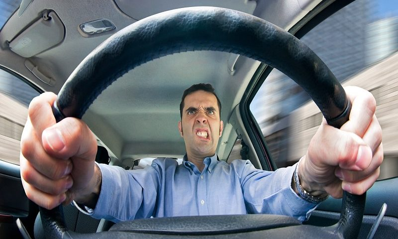 An angry man driving behind the wheel