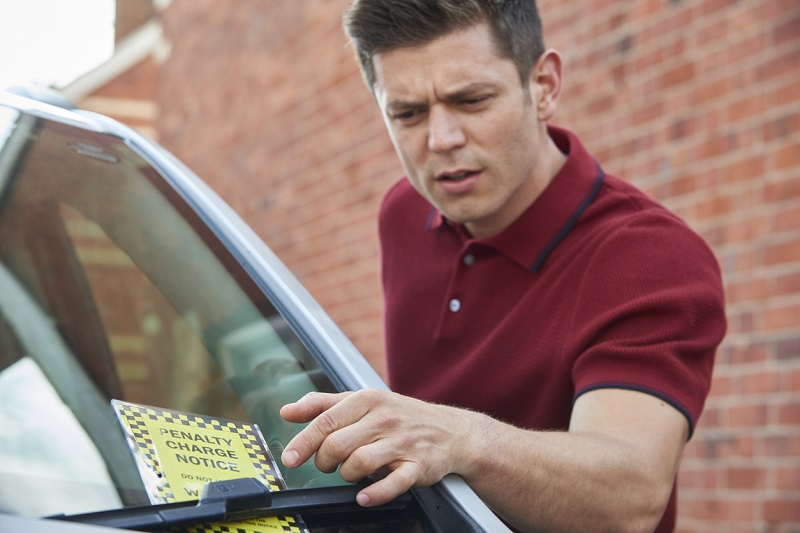 A male driver looks at a parking ticket.