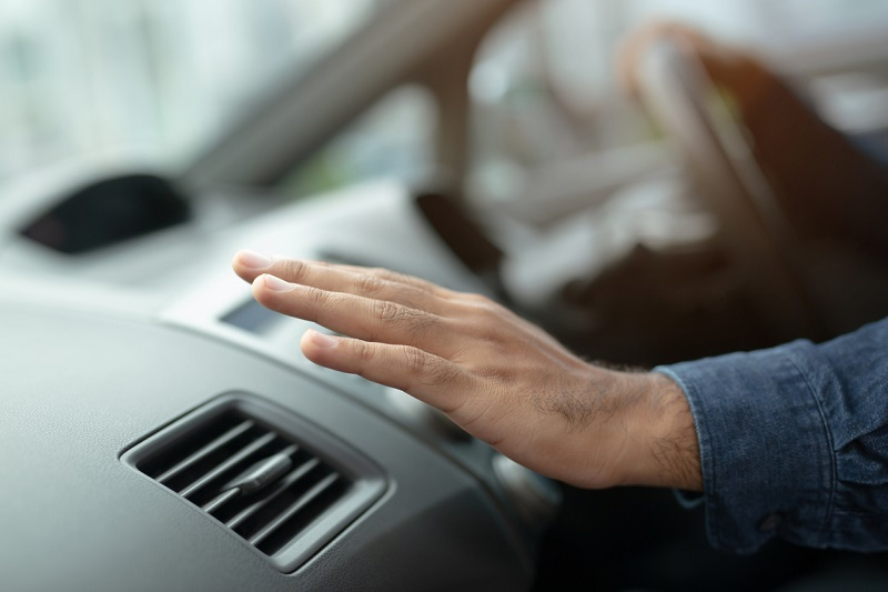 Close-up of male driver's hand checking the air conditioning in a car.