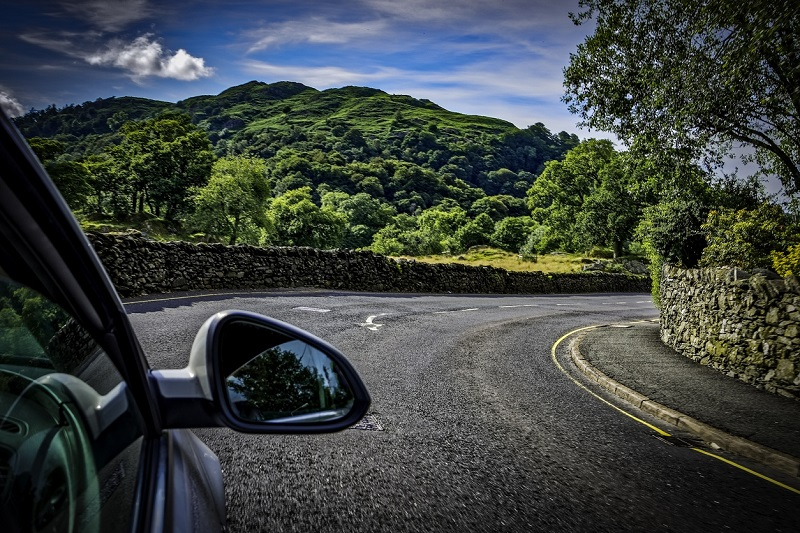 Car on sunny road in Lake District
