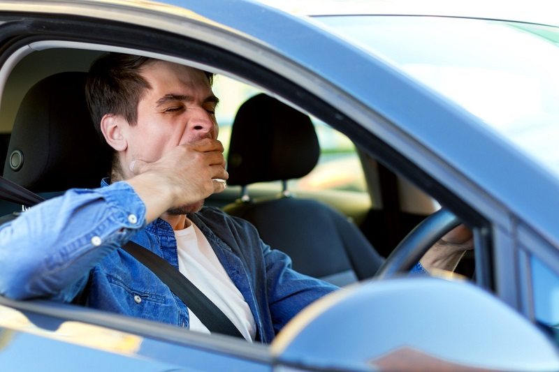 A man yawns while driving