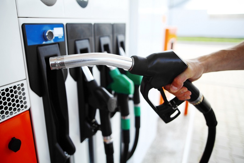 A driver holds a fuel pump at a service station