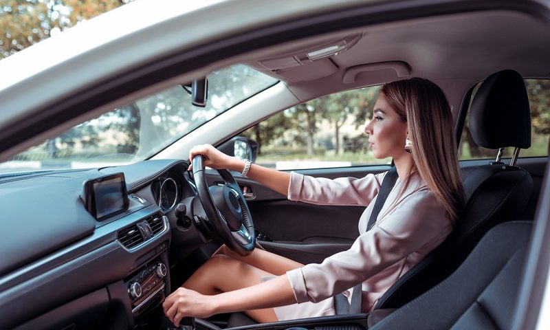 A young driver behind the wheel of her car