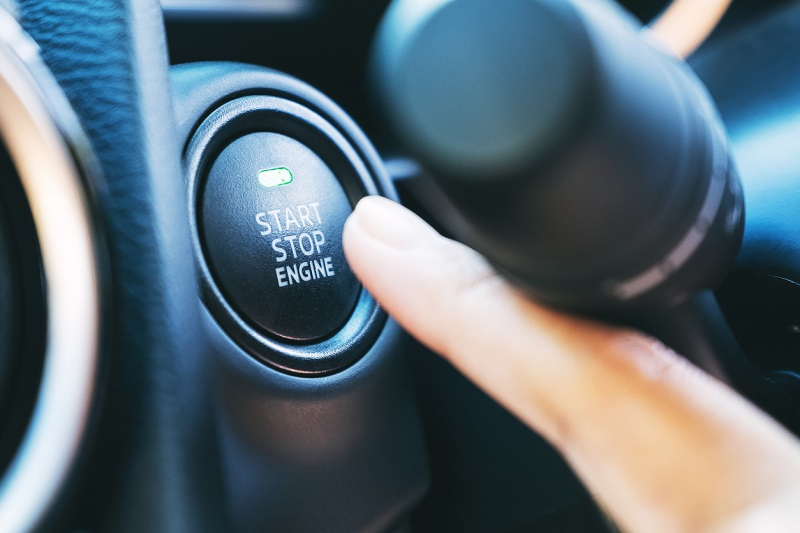 Someone pushing the start engine button on a car dashboard