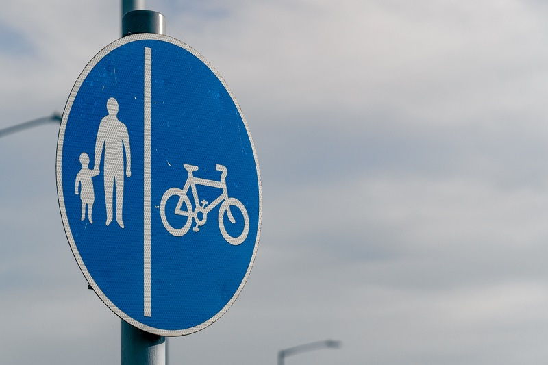 A road sign with images of pedestrians and a bike