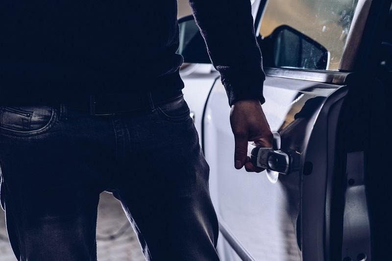 Car thief opening the doors of a stolen car