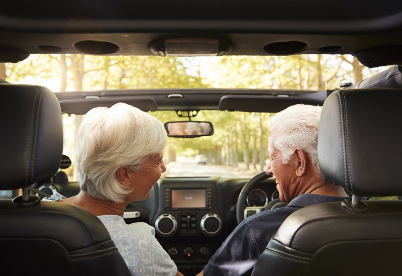Older couple driving in open-top car