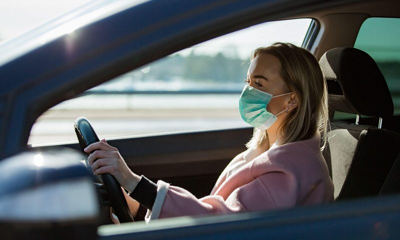 Woman wears Covid-19 mask while driving.