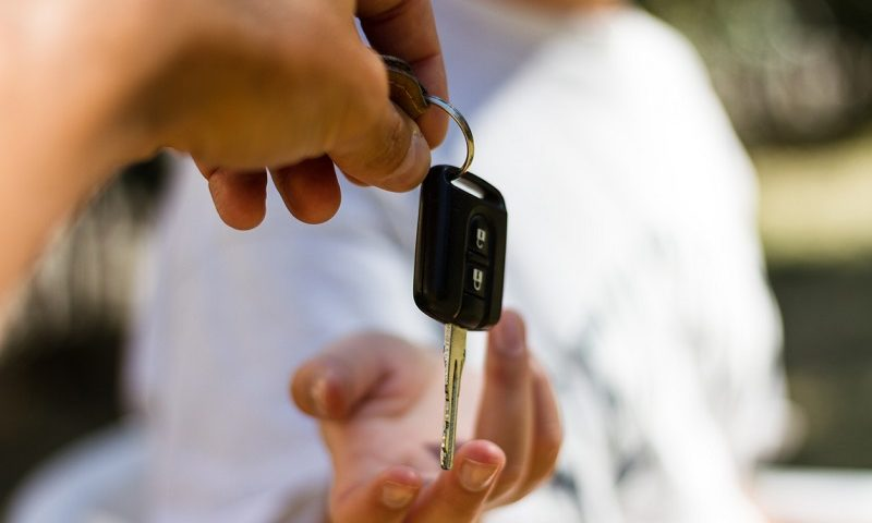 A car key being handed over to a buyer