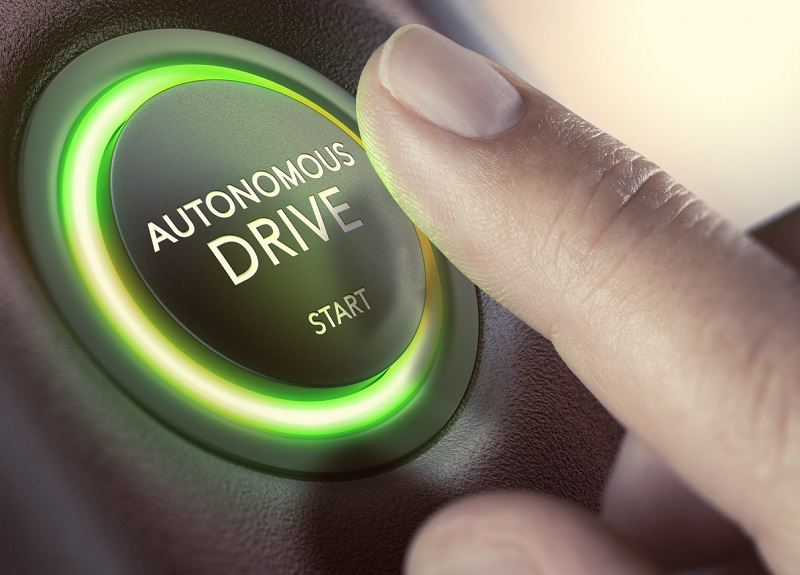 A finger pressing a button to start a self-driving car