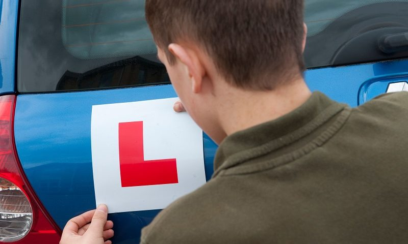 A young person putting an L plate on their blue car