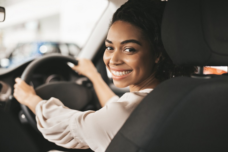 Smiling young woman driving